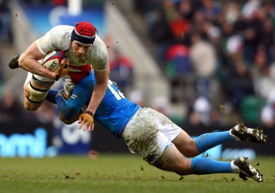 An Italian rugby player tackles an English rugby player in The RBS Six Nations Championship